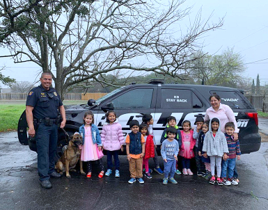 kids together with police standing beside a police car