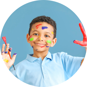 child holding a paint brush with paint stains on his face