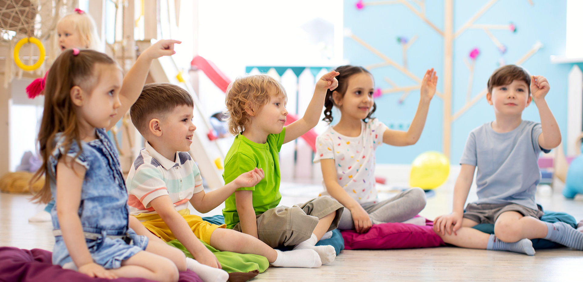 children pointing while sitting down