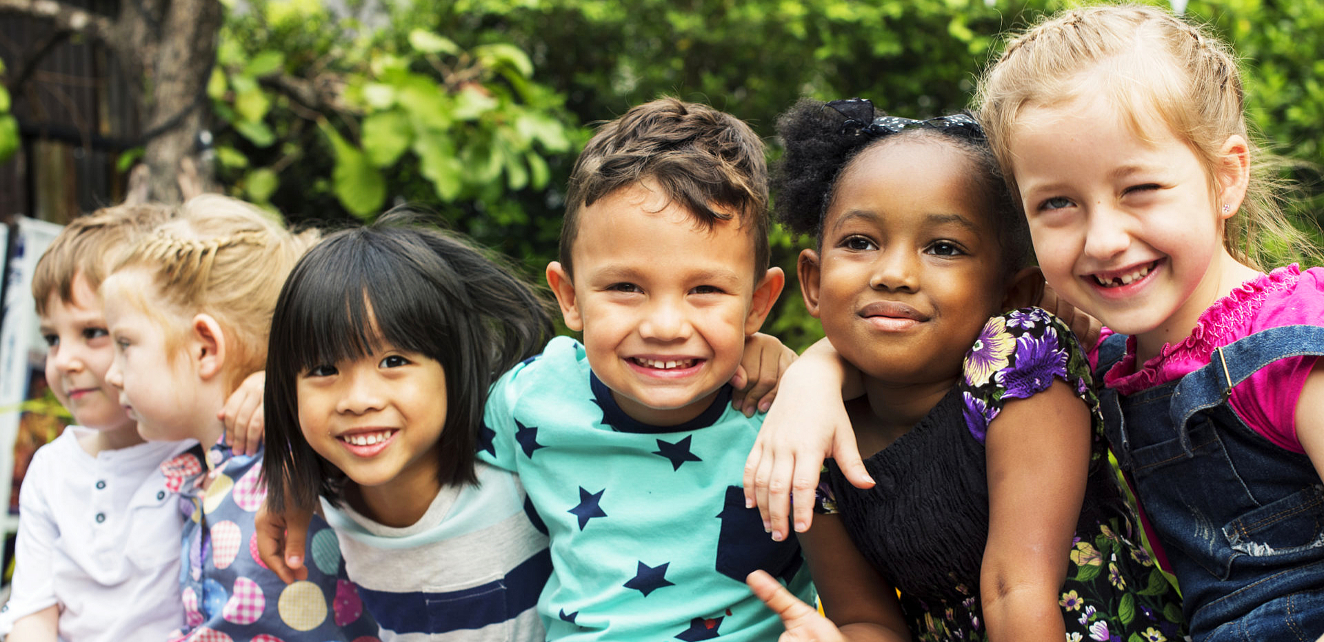 children smiling with arms wrapper around each other