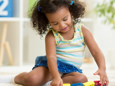 child playing with blocks and small cars