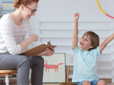 teacher sitting down holding a clipboard with a kid raising both arms in happiness