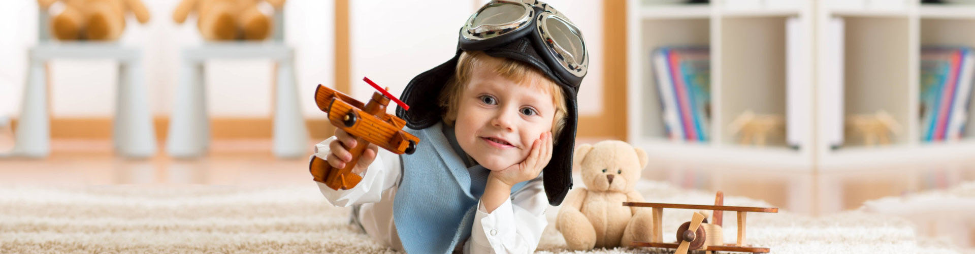 young boy playing with an airplane while wearing a pilot's cap